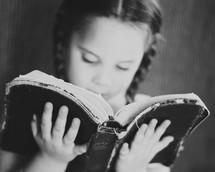 Little girl reading the bible