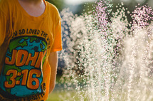 A child in a John 3:16 t-shirt playing in a sprinkler