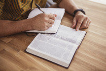 reading a Bible and writing in a journal