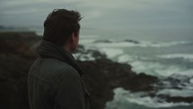 man watching waves crashing into a rocky shore