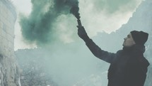 a man standing outdoors holding a smoke flare
