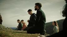 people kneeling in prayer on a mountaintop