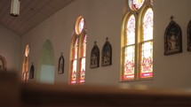 stained glass windows in a church and church pews