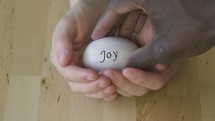 cupped hands holding an egg with the word joy on it