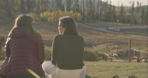 young women sitting outdoors talking at a fall retreat