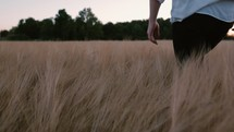 a man walking through a field of tall grass