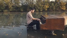 Man playing a piano in water