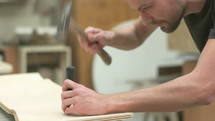 man chiseling holes into wood