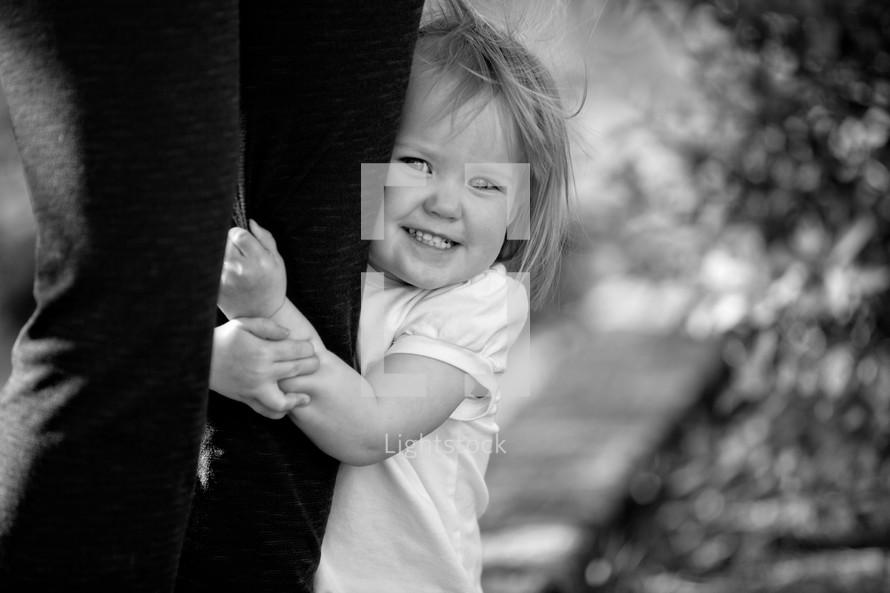 toddler girl holding onto her mother's legs