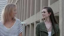 women walking down a downtown sidewalk talking
