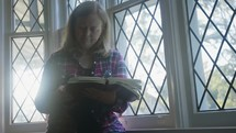 a woman praying at a window and reading a Bible