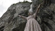 a woman with hands raised standing under a waterfall