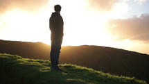 man standing on a mountaintop looking at a sunrise