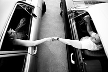 man and woman holding hands through car windows
