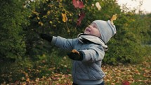 a toddler boy playing in fall leaves