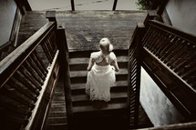 bride walking up wood staircase