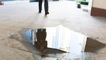 reflection of a businessman in a puddle