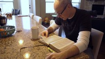 A man reading his Bible in his kitchen