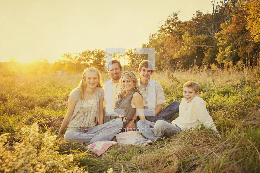 Happy family sitting in grass field