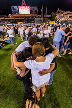 Family in a huddle on baseball field praying salvation crusade holding hugging love trust