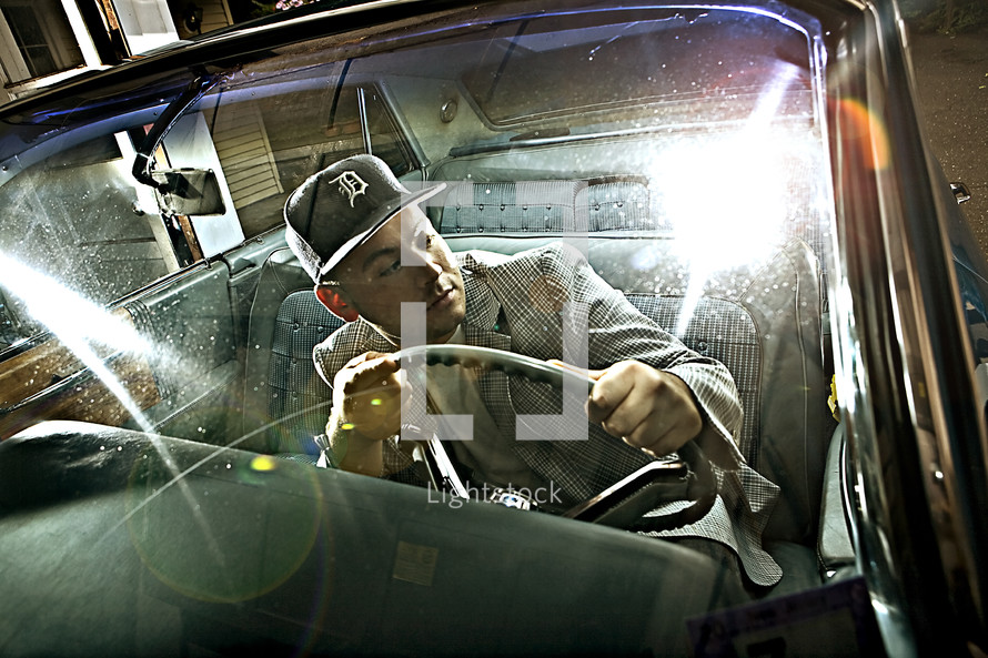 man in a hat driving an old car