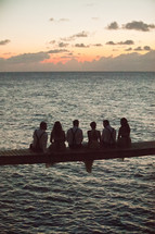group of people sitting on bridge across ocean