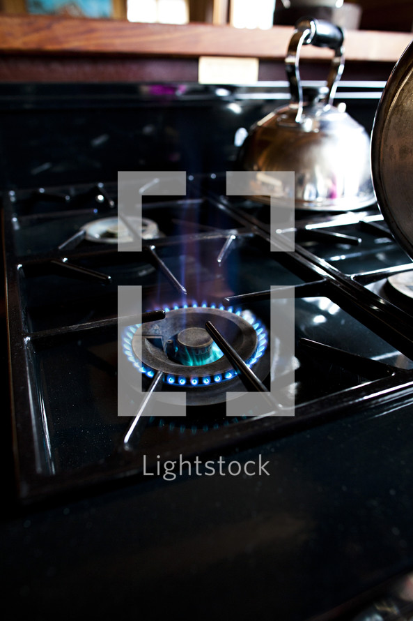 A gas stove top with one burner on, and a copper tea kettle.
