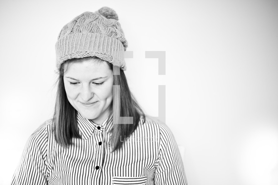 woman wearing a toboggan looking down smiling