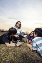 young man reading a Bible to a group of children