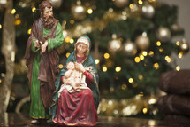 figurines of  Mary, Joseph, and baby Jesus in front of a Christmas tree
