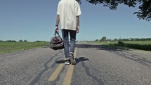 man walking down the middle of a rural road carrying a bag