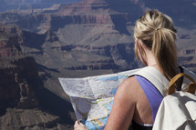 a woman reading a map at the top of a canyon
