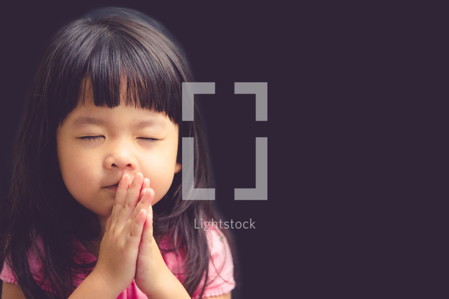 Little asian girl praying in the morning.Little asian girl hand praying,Hands folded in prayer concept for faith,spirituality and religion.Black background.