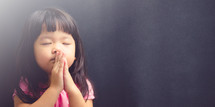 a little girl in prayer
