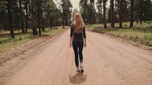 woman walking down a dirt road and tree tops