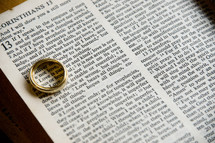 wedding band over the word Love in a Bible