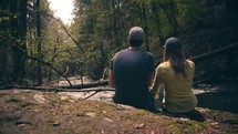 a couple sitting by a river listening to the water flow