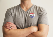 "A man in a gray t-shirt wearing a button reading, ""Vote."""