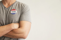 """A man with arms crossed wearing a red white and blue button reading, """"Vote."""""""