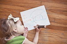 Girl laying on the hardwood floor drawing a picture of Christ's resurrection.
