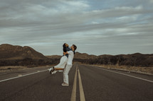 a couple hugging in the middle of a road