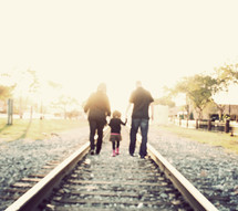 family walking on railroad tracks