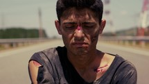 a bloody bruised man walking down a highway