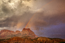 rainbow over a red mountain peak