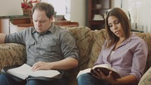 couple sitting on a couch reading Bibles at a Bible study