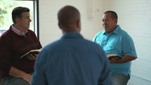 men reading Bibles and discussing scripture