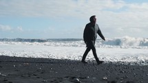 a man in a coat and boots walking on a beach in winter