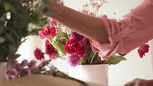 a woman arranging flowers for mother's day