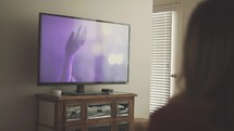 a woman watching a worship service on her tv