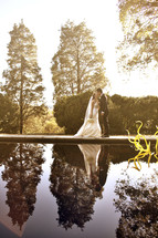 A bride and groom kiss next to a pond